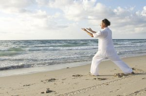 Man dressed in white doing tai qi on the beach at low tide. Illustrating the environmentally-conscious health and wellness tribe seeking pristine outdoor spaces in our environment for exercise and relaxation.