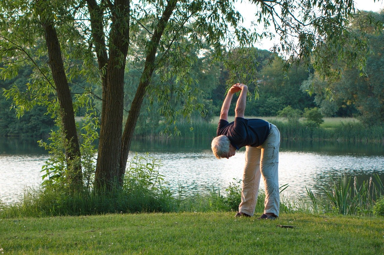 Man doing yoga near a pond. Illustrating the environmentally-conscious health and wellness tribe's desire for pristine environments for exercise and relaxation