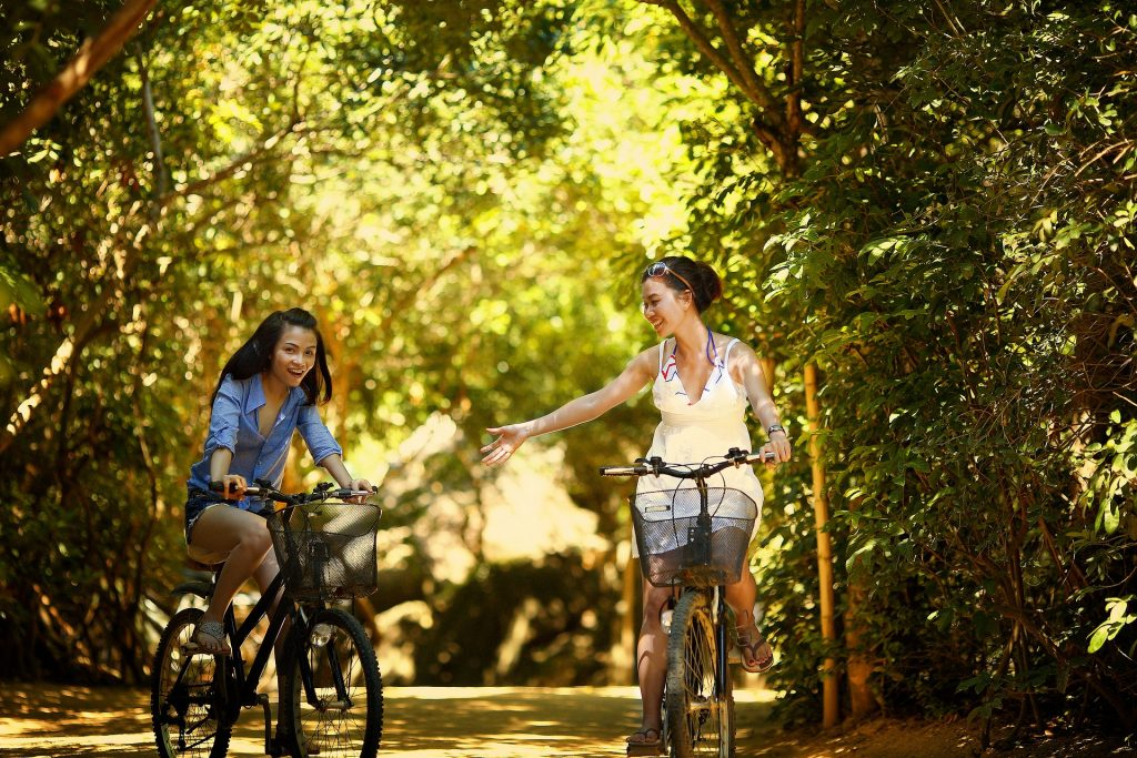 Two girls riding bicycles - one girl is extending a helping hand - customer journey